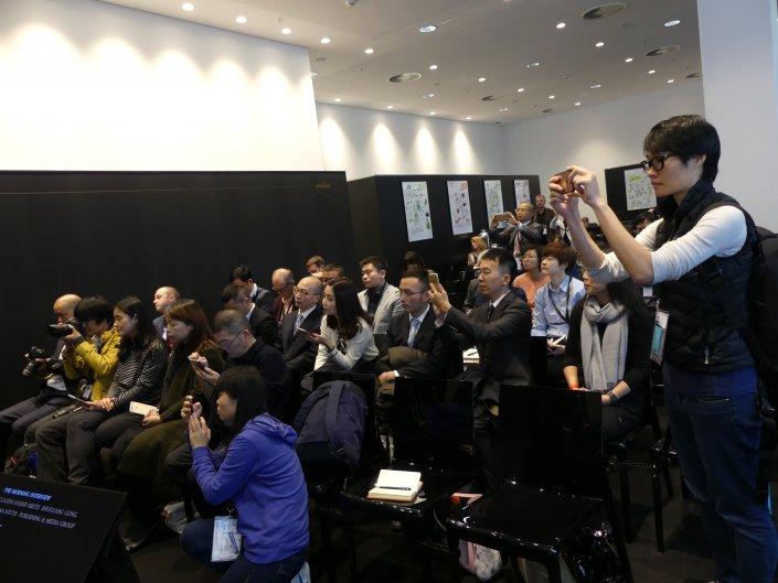 ...und internationales Publikum. Hier ist eine Gruppe asiatische Buchschaffende sichtbar fasziniert von einem Vortragenden im Business Club Messe.